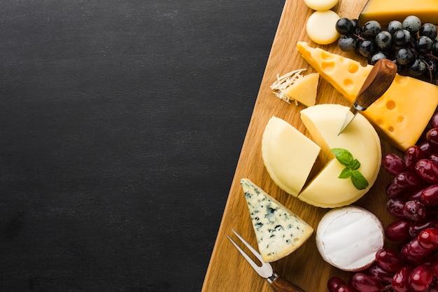 Mezcla plana de queso gourmet y uvas en tabla de cortar con espacio de copia
