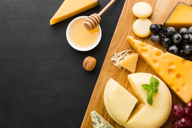 Mezcla plana de queso gourmet y uvas en tabla de cortar con miel