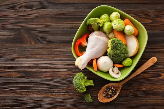 Mezcla plana de verduras y muslo de pollo en un tazón con espacio de copia