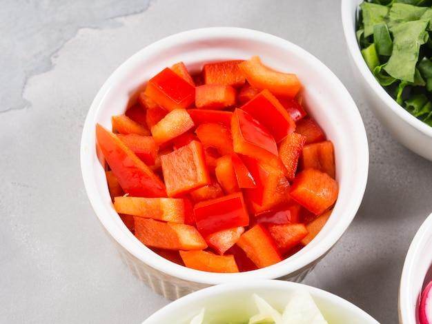 Mezcla de tazones de verduras para ensalada o bocadillos en gris. concepto de desintoxicación de la dieta. cocinar con pimientos