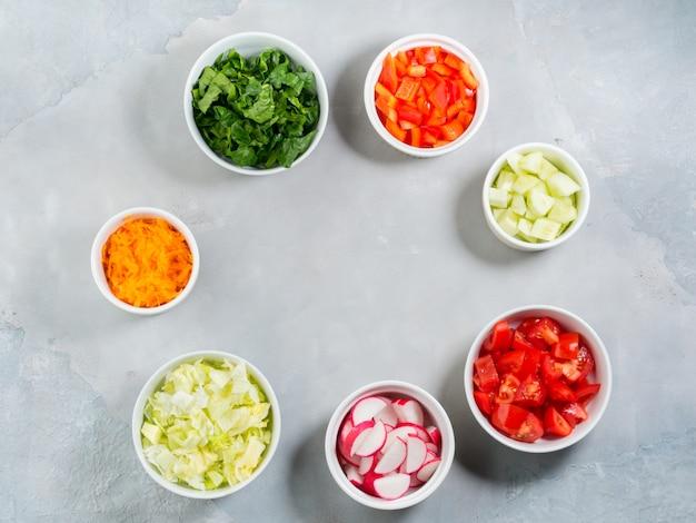 Mezcla de tazones de verduras para ensalada o bocadillos en gris. dieta concepto detox