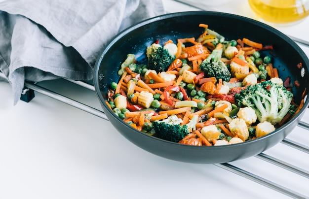 Mezcla de verduras fritas en una sartén negra sobre la mesa blanca. comida sana