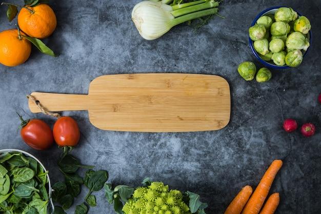 Una mezcla de verduras y frutas de temporada rojas y verdes colocadas alrededor de una tabla para cortar madera