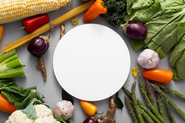 Mezcla de verduras laicas planas con círculo en blanco