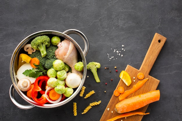 Mezcla de verduras y muslo de pollo en una sartén con zanahoria en la tabla de cortar