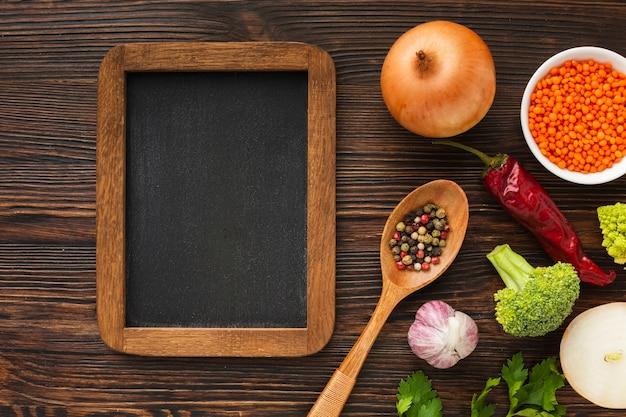 Mezcla de verduras planas y pizarra en blanco
