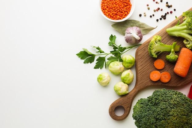 Mezcla de verduras planas en tabla de cortar con espacio de copia