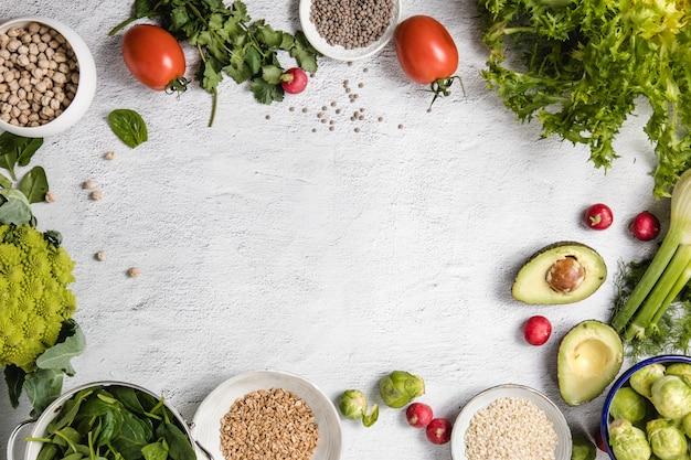 Una mezcla de verduras de temporada y granos enteros dispuestos sobre un fondo blanco con copyspace