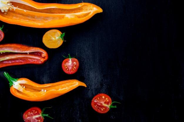 Mezclado de medio pimiento rojo y amarillo con una rama verde cerca de tomate cherry sobre un fondo negro. vista superior. marco. copia espacio