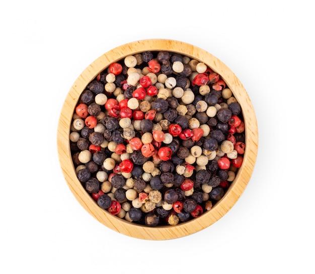Mezclado de pimientos picante, rojo, negro, blanco en un tazón de madera aislado sobre fondo blanco. vista superior