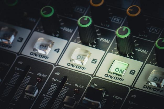 Mezclador de audio profesional con perillas y barras deslizantes para ajustar el sonido.