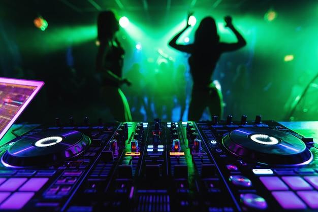 Mezclador de dj en una discoteca con chicas de baile go-go