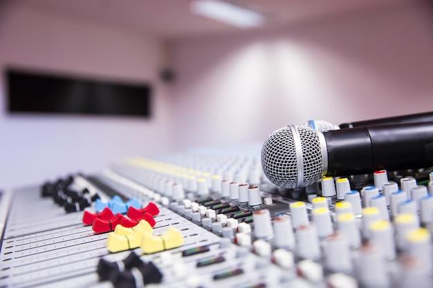 Mezclador de sonido y micrófonos en estudio.