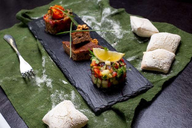 Mezclar aperitivos fríos ensalada de mangal nueces kuku bollos de ensalada verde vista lateral