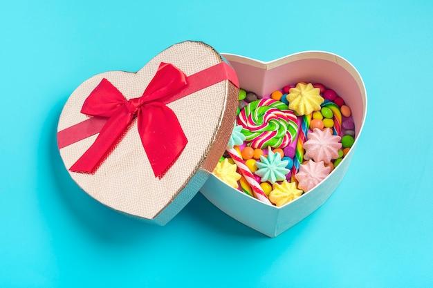 Mezclar dulces de chocolate se encuentran en forma de corazón de caja de regalo en colores de fondo
