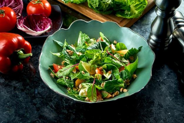 Mezclar la ensalada con caqui, mozzarella, espinaca y nueces, servida en un cuenco verde sobre una mesa de mármol oscuro. ensalada de verduras. comida de restaurante