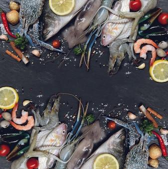 Mezclar mariscos frescos marinos crudos con hierbas y especias limón en oscuro
