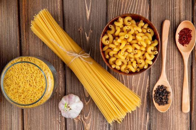 Mezclar pastas en la mesa de madera espaguetis fellini chifferi ajo sumakh pimienta vista superior