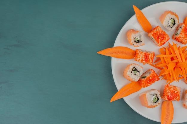 Mezclar sushi con rodajas de zanahoria en la placa blanca.