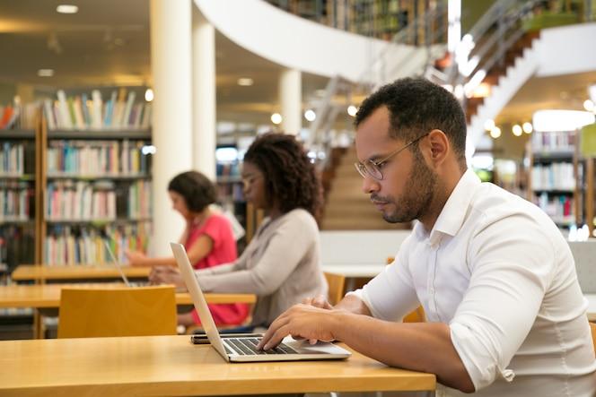 Mezcle a los alumnos que corren trabajando en la computadora en una biblioteca pública