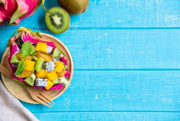 Mezcle la ensalada de frutas tropicales servida en media fruta de dragón en la mesa de madera