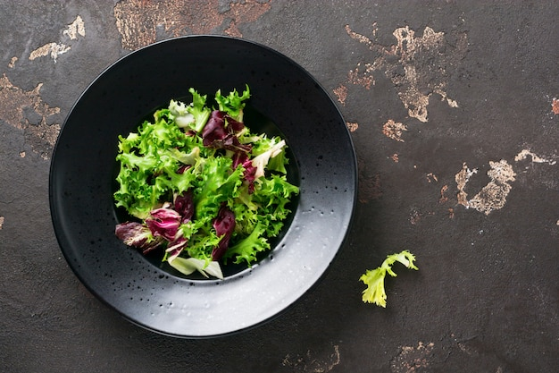 Mezcle hojas frescas de rúcula, lechuga, espinaca, remolacha para ensalada sobre un fondo de piedra oscura. enfoque selectivo.