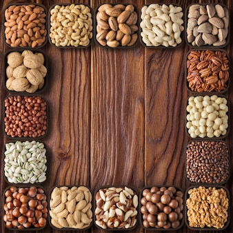 Mezcle nueces y semillas en tazones de madera, vista superior. fondo de alimentos saludables en la mesa.