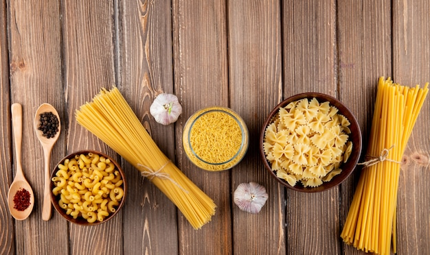 Mezcle las pastas en la mesa de madera chifferi spaghetti fellini farfale linguini ajo sumakh pepper vista superior