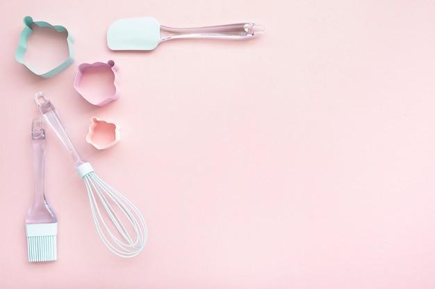 Mezcle los utensilios de respaldo sobre fondo rosa, vista superior