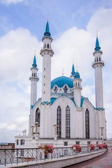 Mezquita kul sharif en el kremlin de kazán contra un cielo azul con nubes blancas y flores rosadas en primer plano
