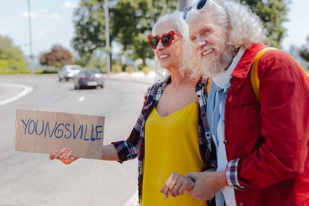 Mi amor. hombre de edad positiva sosteniendo la mano de su esposa mientras hace autostop junto con ella