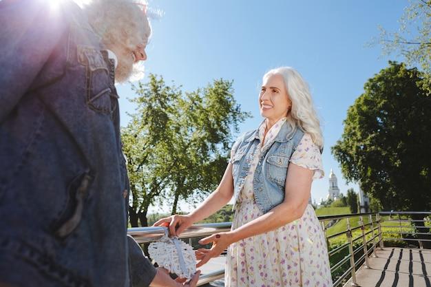 Mi amor. mujer de edad agradable sonriendo a su marido mientras está de pie en el puente con él