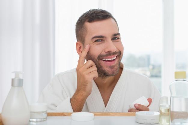 Mi cara. hombre guapo alegre sonriendo mientras se pone crema en la cara