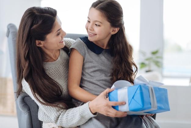 Para mi chica. mujer feliz agradable positiva sonriendo y mirando a su hija mientras prepara un regalo para ella