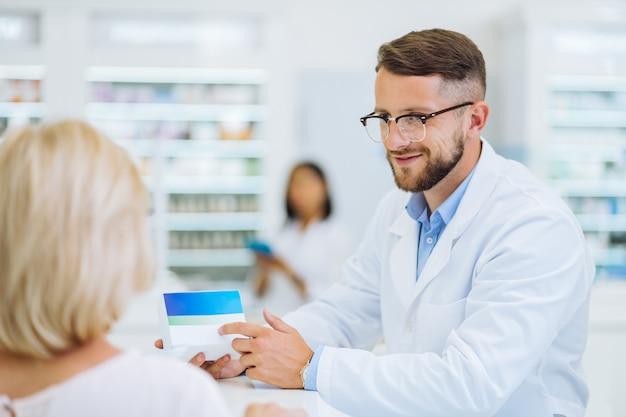 Mi cliente. farmacéutico guapo manteniendo una sonrisa en su rostro mientras mira a la mujer rubia