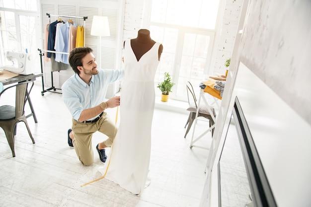 Mi creación. modista barbudo inspirado sonriendo y haciendo un vestido nuevo