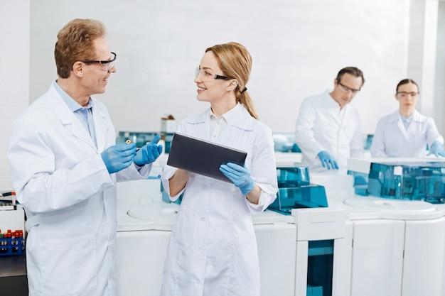 Mi dispositivo. dos asistentes de laboratorio parados uno frente al otro y manteniendo una sonrisa en las caras mientras hablan sobre el experimento