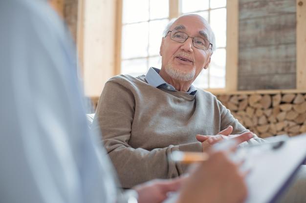 A mi edad. doctor usando el portapapeles mientras toma notas y escucha a un hombre mayor agradable y alegre