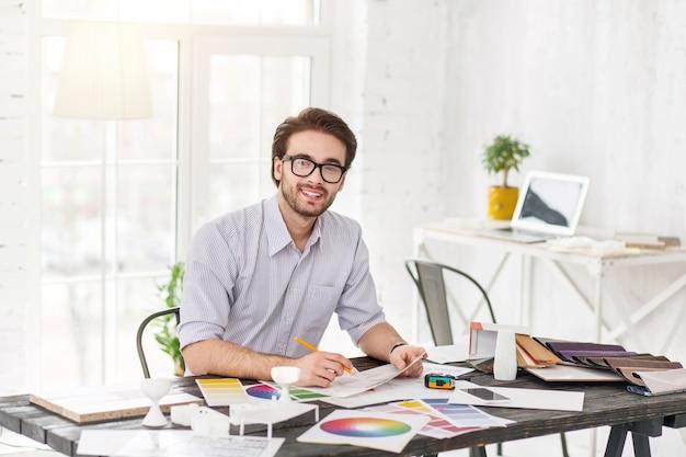 Mi inspiración. apuesto hombre encantado sentado a la mesa y sosteniendo una hoja de papel y un lápiz