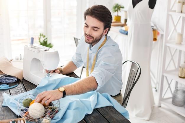 Mi inspiración. encantado de sastre de pelo oscuro sonriendo y trabajando en una máquina de coser