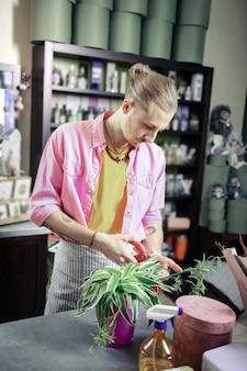 Mi lugar de trabajo. apuesto joven diseñador vistiendo elegante uniforme y cuidando flor
