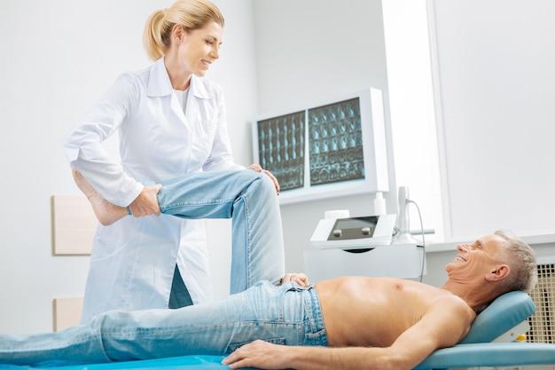 Mi medico. anciano alegre inteligente acostado en la cama médica y sonriendo mientras mira a su médico