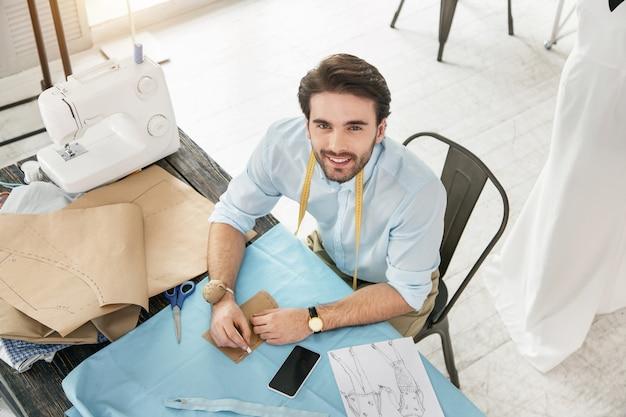 Mi negocio. contenido modista morena sentada a la mesa y confeccionando un vestido nuevo