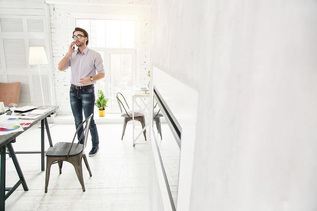 Mi negocio. exitoso joven empresario hablando por teléfono mientras está de pie en la oficina