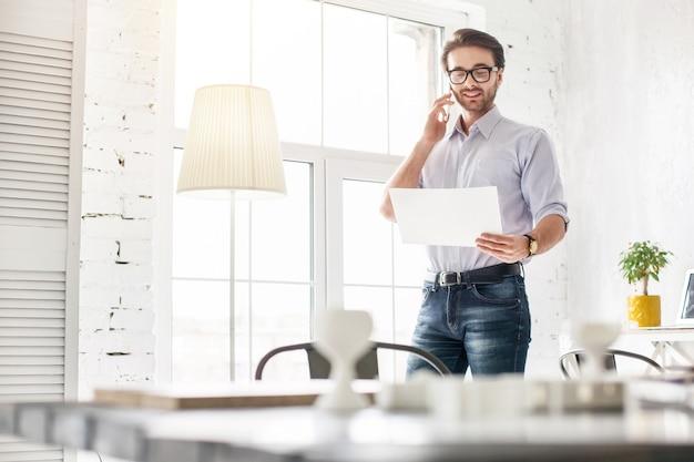 Mi nueva oficina. hombre joven inspirado hablando por teléfono y sosteniendo una hoja de papel