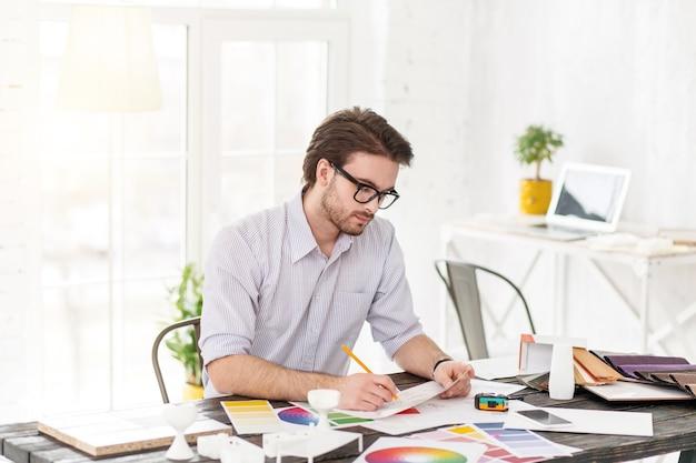 Mi obra favorita. atractivo hombre concentrado sentado a la mesa y sosteniendo una hoja de papel y un lápiz