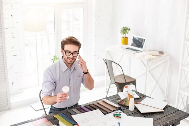 Mi oficina. exuberante hombre de cabello oscuro hablando por teléfono y sosteniendo un objeto blanco