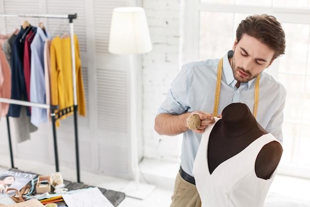 Mi oficina. modista serio de pelo oscuro trabajando en su oficina y haciendo un vestido nuevo