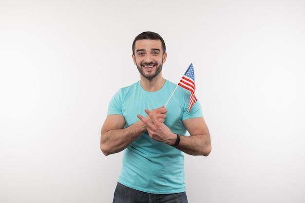 Mi pais. agradable buen aspecto que muestra el signo v mientras sostiene una bandera estadounidense