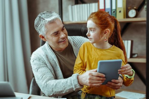 Mi papá. linda chica linda mirando a su padre mientras está sentado junto a él